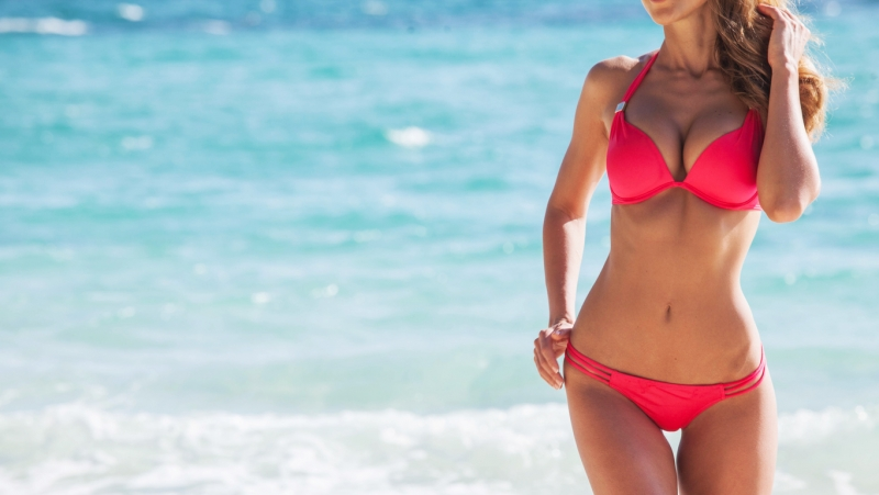 A skinny woman in a pink bikini walks along the beach